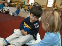 Samuel Habib, 3, sits in his supportive corner chair and smiles at a friend at Shaker Road School in Concord when he was a pre-schooler.  Samuel, now 7, has cerebral palsy.  His parents, Dan Habib and Betsy McNamara are committed to full inclusion for Samuel in the community, family and at school.    Dan Habib photo