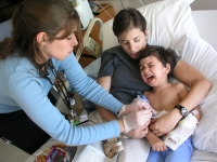 Samuel Habib is held by his mother, Betsy McNamara, as a nurse changes the dressing soon after Samuel, then 3, had a g-tube inserted into his stomach to improve his ability to take in foods and medicine.  Dan Habib photo