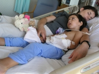 Samuel Habib rests with his mother, Betsy McNamara soon after Samuel, then 3, had a g-tube inserted into his stomach to improve his ability to take in foods and medicine.  Dan Habib photo