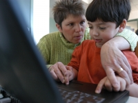 Samuel works on a laptop with physical therapists Colleen Sullivan in her office on March 31, 2005.  (Dan Habib/Concord Monitor)