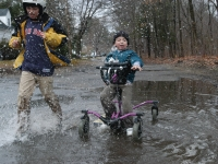 Samuel and Isaiah play in a puddle outside their home.  (Dan Habib/Concord Monitor)