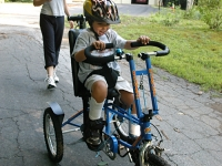 Samuel rides his trike near his home with his mother Betsy McNamara.  Dan Habib photo