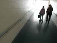 """At the end of the school day, Alana walks down a hallway with an aide. """"I think that having (an aide) with her all these years probably didn't help her in making friends,"""" says special educator Karen Madeiros. Dan Habib photo"""