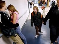 Alana walks with her aide through the hallways of Pembroke Academy near other students.  Dan Habib photo
