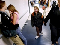 Alana walks with her aide through the hallways of Pembroke Academy near other students.  Dan Habib photo
