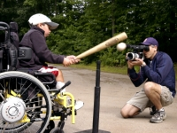 """Samuel Habib, 7, sits in his power-assist wheelchair and smacks a t-ball off of a batting T.  His father, filmmaker Dan Habib, videotapes him with a Canon XL1S MiniDV Digital Camcorder in their Concord, NH, driveway. While making the film INCLUDING SAMUEL, Habib says he continually asked himself, """"When do I play filmmaker? When do I just play with my kids?""""   MANDATORY CREDIT: Photo by Isaiah Habib (Samuel's brother, age 11), August, 2007. From the film, Including Samuel, www.includingsamuel.com"""