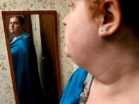 """Emily Huff looks in the mirror wearing a cape she just made. """"It gives me courage,"""" she said."""