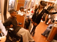 """Keith Jones chats with a woman on the """"T"""" subway as he makes his way around his home town of  Boston.  Dan Habib photo"""