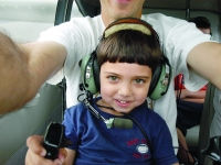 Samuel grabs the steering wheels of the sea plane owned by his grandfather, Walter McNamara, as he sits with his father, Dan Habib, shortly before take off.  Dan Habib photo